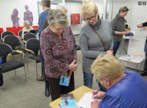Na pierwszym planie autorka podpisuje książki, przy stoliku dwie kobiety czekające na książkę
