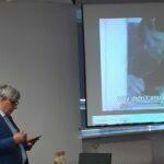 Wiesław Kot, w tle ekran z wyświetlanym filmem