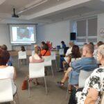 Publiczność zgromadzona na spotkaniu. W tle ekran z filmem